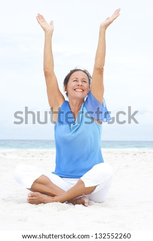 Portrait attractive mature woman sitting cheerful and happy with arms up at beach, wearing blue blouse, with ocean and white overcast sky as blurred background and copy space. - stock photo