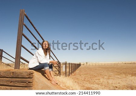 Portrait attractive mature woman sitting relaxed at metal fence line in rural farming area in outback Australia, with dry arid agricultural country and blue sky as background and copy space.