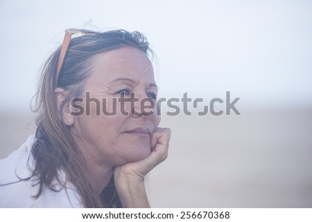 Portrait attractive mature woman sitting thoughtful relaxed outdoor with chin on hand, blurred background and copy space. - stock photo