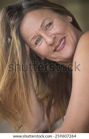 Portrait attractive mature woman smiling confident relaxed with hand seductive in long brunette hair, blurred background. - stock photo