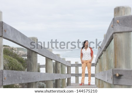 Portrait attractive mature woman standing relaxed and confident on wooden boardwalk at sea, enjoying active retirement and holiday, with coastline and ocean as blurred background and copy space.
