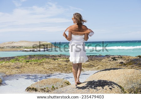 Portrait attractive mature woman standing relaxed in white summer dress on rocks at beach, turquoise colored ocean at Bay of Fire, Tasmania, with blue sky and horizon as background and copy space.