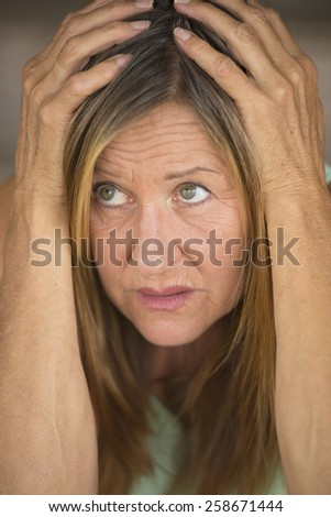 Portrait attractive mature woman, stressed, anxious, scared, unhappy frightened upward look, hands covering head, blurred background. - stock photo
