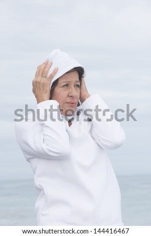 Portrait attractive mature woman wearing white  jumper with hood, freezing in cold seasonal autumn or winter weather at ocean, with blurred background of sea.