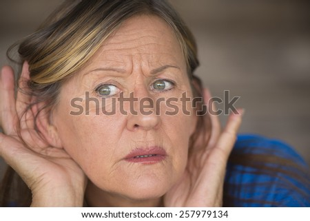 Portrait attractive mature woman with hands at ears listening with curious and anxious facial expression to loud noise or sound, blurred background. - stock photo