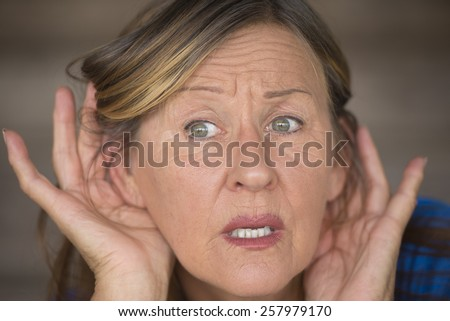 Portrait attractive mature woman with hands at ears listening with curious, interested and anxious facial expression to loud noise or sound, blurred background. - stock photo