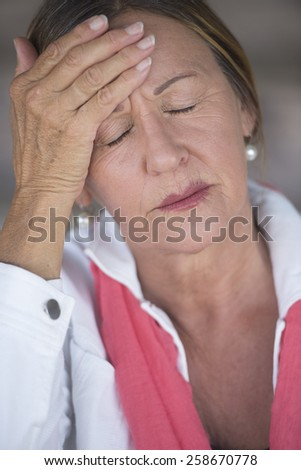 Portrait attractive mature woman with headache, migraine, stressful menopause, closed eyes, blurred background. - stock photo