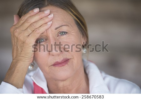 Portrait attractive mature woman with headache, painful migraine, stressful menopause, blurred background, copy space.