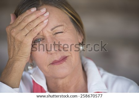 Portrait attractive mature woman with headache, painful migraine, stressful menopause, closed eyes, blurred background, copy space.