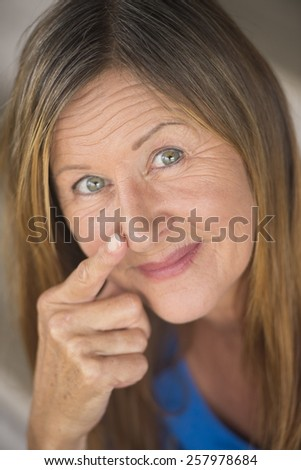 Portrait attractive mature woman with serious happy confident facial expression, upward look smile, finger pointing to nose, blurred background. - stock photo