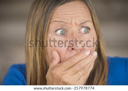Portrait attractive mature woman with shocked, anxious, fearful facial expression, covering mouth with hand, blurred background. - stock photo