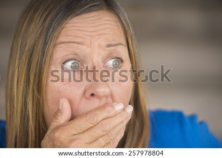 Portrait attractive mature woman with shocked, surprised, anxious, fearful expression, covering mouth with hand, blurred background. - stock photo