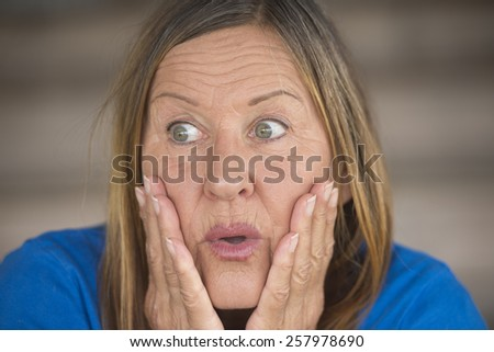 Portrait attractive mature woman with shocked, surprised, anxious, frightened facial expression, blurred background. - stock photo