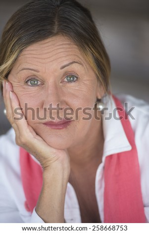 Portrait attractive mature woman with thoughtful worried concerned expression, alone with hand resting on chin, blurred background.