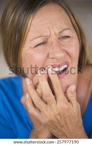 Portrait attractive mature woman with tooth ache, in pain, stressed expression, closed eyes, blurred background, - stock photo