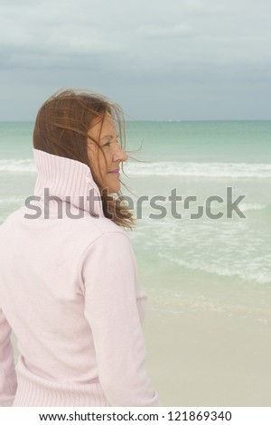 Portrait attractive middle aged woman enjoying active retirement, standing happy smiling at beach, isolated with ocean as blurred background.