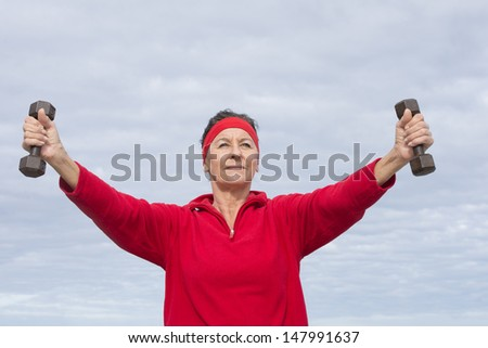 Portrait attractive middle aged woman, happy, relaxed, sporty, friendly, positive, successful, exercising outdoor, wearing red sweater and headband, with sky as copy space and blurred background.