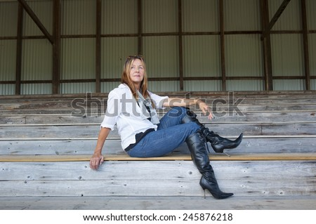 Portrait attractive senior woman posing outdoor sitting on grandstand bench in sexy high heel stiletto boots and jeans, confident and relaxed, copy space. - stock photo