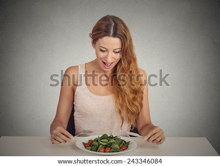 portrait attractive smiling young woman eating green salad isolated on grey wall background studio shot. healthy fresh food diet nutrition concept   - stock photo
