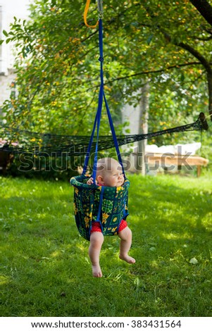 portrait , baby in a swing, summer - stock photo