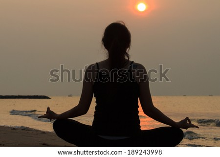 portrait back view of Asian woman practicing yoga at peace sea in morning - stock photo
