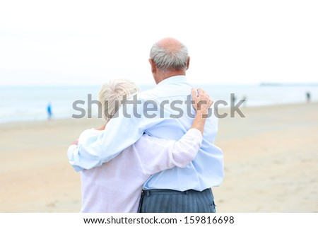 Portrait, back view of caring couple of two seniors, a man and his wife, standing together on a sandy peaceful beach looking at the ocean - stock photo