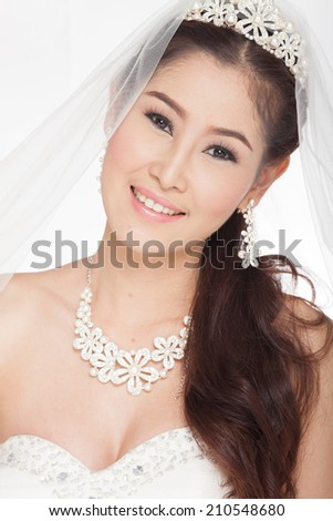 portrait beautiful asian woman in white wedding dress with veil,smiling in studio light ,white background