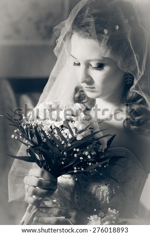 Portrait beautiful bride with bouquet of flowers on luxury interior in wedding day.