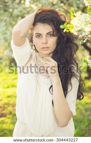 Portrait beautiful brunette woman in sunset light. Woman on nature background summer / spring. Enjoying the nature. Young woman arms raised enjoying the fresh air. Fashion woman model.