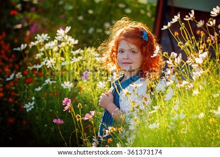Portrait Beautiful curly-headed red Girl in the Blossoming garden in a clear Sunny Day - stock photo