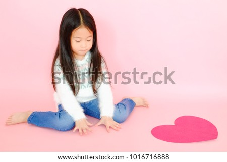 Portrait beautiful cute asian child girl on pink background with red heart sign, valentine day in love concept