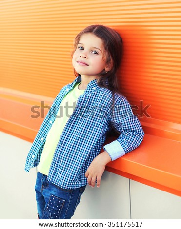Portrait beautiful little girl child wearing a checkered shirt over colorful background