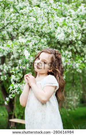 Portrait beautiful little girl near blossoming apple-tree - stock photo