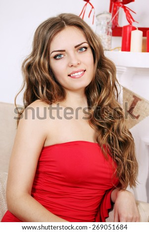 portrait Beautiful long-haired woman near the fireplace