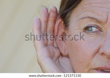 Portrait beautiful looking mature woman looking curious while listening with hands close to ears, isolated outdoor with blurred background. - stock photo