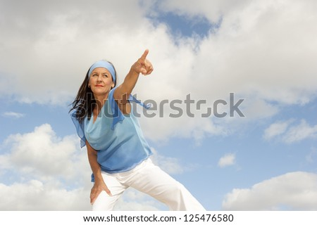 Portrait beautiful looking middle aged woman confident, determined and successful smiling, focused pointing finger, isolated with cloudy blue sky as background and copy space. - stock photo