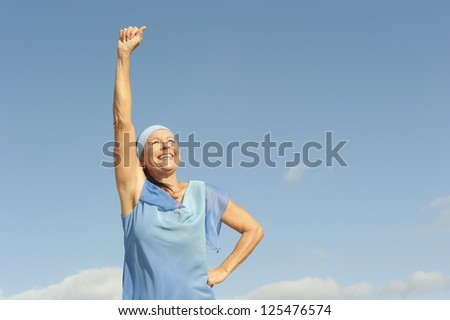 Portrait beautiful looking middle aged woman confident, happy and successful smiling, enjoying active retirement, isolated with blue sky as background and copy space.
