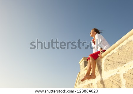 Portrait beautiful looking middle aged woman sitting relaxed and happy smiling on limestone wall, enjoying sunny day, isolated with blue sky as background and copy space. - stock photo