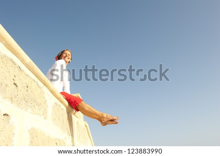 Portrait beautiful looking middle aged woman sitting relaxed cheerful and happy smiling on limestone wall, enjoying sunny day, isolated with blue sky as background and copy space. - stock photo