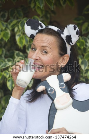 Portrait beautiful mature woman happy relaxed friendly drinking glass of milk, funny cow ears on head and wooden cow in arm outdoor with blurred background. - stock photo