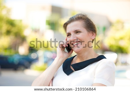 Portrait Beautiful mature woman or businesswoman in her forties talking on a cell phone, having pleasant conversation, receiving good news, outdoors background. Positive facial expressions - stock photo