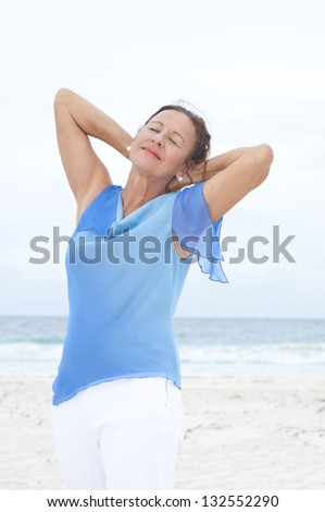 Portrait Beautiful mature woman peaceful and happy at beach, wearing blue blouse, with ocean and white overcast sky as blurred background and copy space. - stock photo