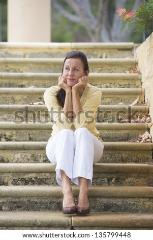 Portrait beautiful mature woman sitting outdoor on wide limestone steps in park, looking sad and lonely, depressed and stressed, with copy space and blurred background. - stock photo