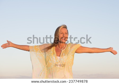 Portrait beautiful mature woman, smiling joyful, successful, confident and happy with arms up, clear sky as outdoor background and copy space. - stock photo