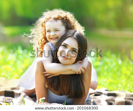 Portrait beautiful mom and daughter resting in summer day - stock photo