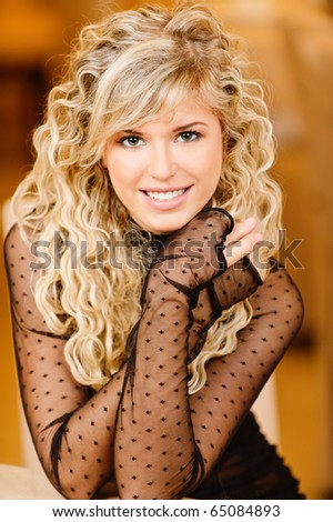 Portrait beautiful smiling young curly-haired women in beautiful black evening dress, against beautiful interior.