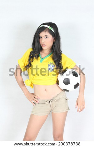 Portrait Beautiful woman hold ball with wearing Brazil football top - stock photo