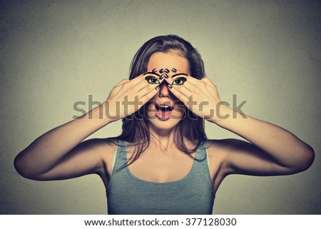 Portrait beautiful young woman with eyes painted on her hands isolated on gray wall background  - stock photo