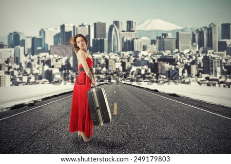 Portrait beautiful young woman with suitcase baggage standing on road waiting for a ride isolated on city skyscraper megapolis mountain skyline background. New urban life beginning adventure concept