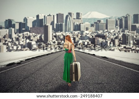 Portrait beautiful young woman with suitcase baggage walking on road talking on mobile phone isolated city skyscraper megapolis mountain skyline background. New urban life beginning adventure concept